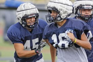 Saugus' James Stirwalt, left, smiles as he chases down teammates during a warmup exercise at practice on Tuesday, August 15, 2017. Katharine Lotze/The Signal