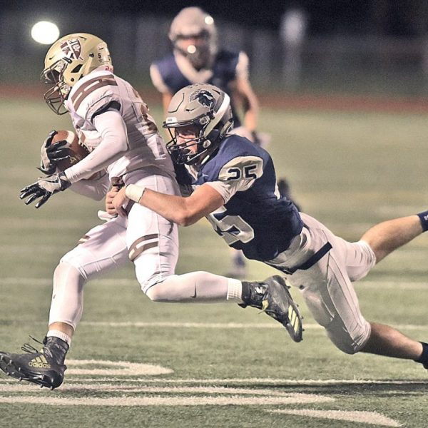 Saugus' Tyler Hampsten (25) brings down St. Francis running back, Elijah Washington (25) for a loss at COC on Friday. Dan Watson/for The Signal