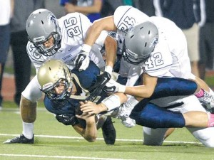 Saugus defenders Michael Parker (25) and Dylan Ayache (42) tackle West Ranch quarterback Chase Killingsworth on Friday at Valencia High School.